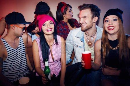 Photo pour Amis excités Clubbing à Swag Party. Groupe de jeunes hommes élégants et femmes détendre à super fête, rire, boire de l'alcool et profiter ensemble de temps - image libre de droit