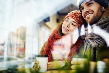 Couple looking through window in cafe