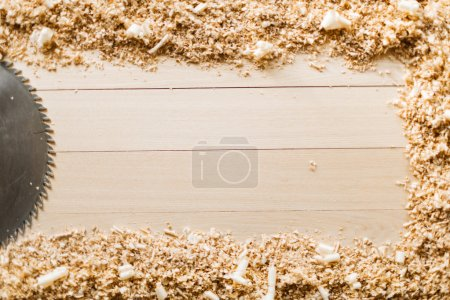 Saw-blade and sawdust on background