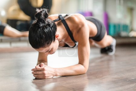 Photo for Female athlete doing plank exercise on the floor - Royalty Free Image