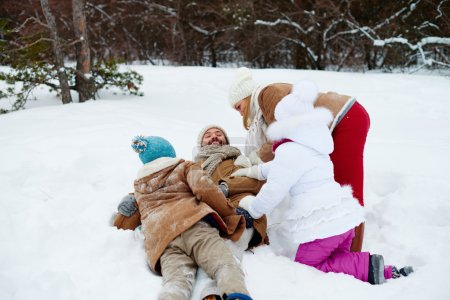 Playful family having fun in snowdrift