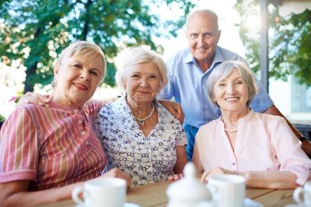 Smiling senior people looking at camera