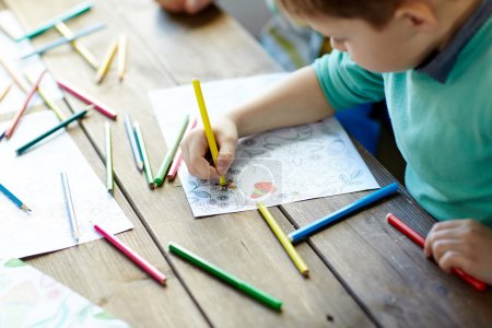 Little boy drawing with color crayons