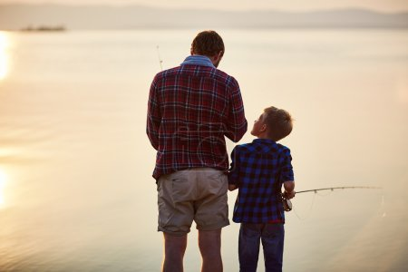 Little boy and his father fishing at sunset