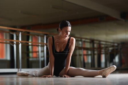 Photo for Ballerina making effort during stretching in ballet class - Royalty Free Image