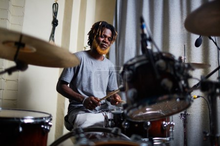 African-american performer playing on drum-set