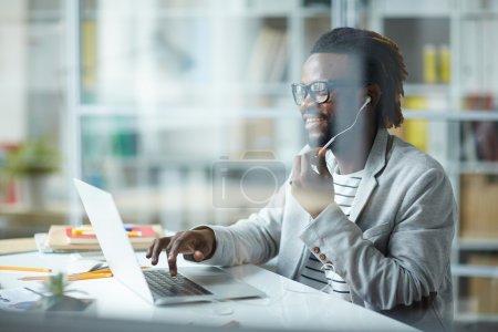Photo pour Jeune homme d'affaires afro-américain charismatique assis au bureau moderne riant alors qu'il parle à quelqu'un utilisant un casque et prenant des notes dans un ordinateur portable, derrière un mur de verre tourné - image libre de droit