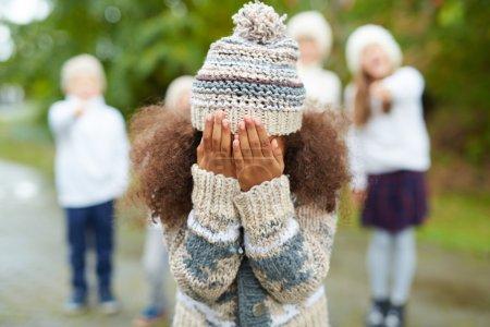 Photo pour Fille qui pleure, cachant son visage tandis que ses camarades de classe se moquant de lui - image libre de droit