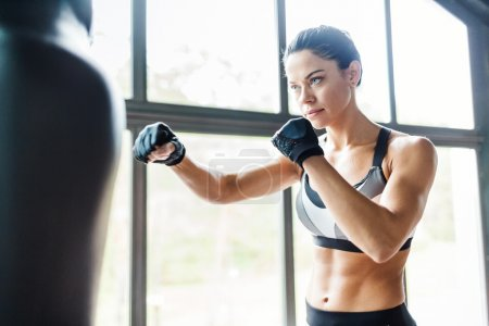 Photo for Female fighter practicing kickboxing exercise in gym - Royalty Free Image
