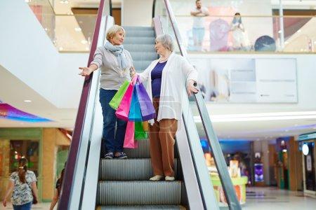 Senior women descending on escalator and talking