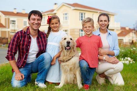 Photo pour Membres de la famille et de leur chien assis sur l'herbe de la maison neuve - image libre de droit