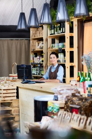 Small business owner standing by cashdesk