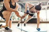 Trainer and woman exercising with dumbbells
