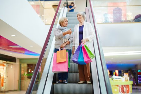 Senior women on escalator in shopping center