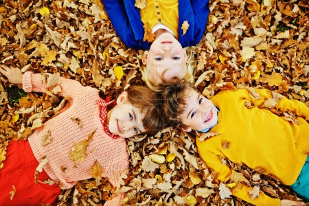 Photo for Above view of three smiling children, two boys and girl, in bright clothes enjoying warm autumn day, playing in park and lying in pile of fallen leaves and looking at camera - Royalty Free Image