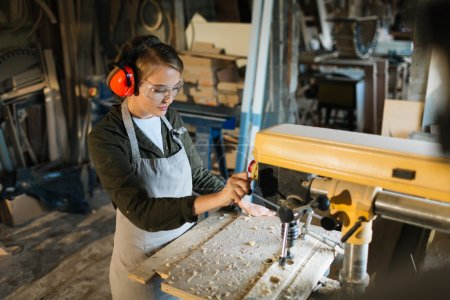 Young woman woodworking by drill-machine