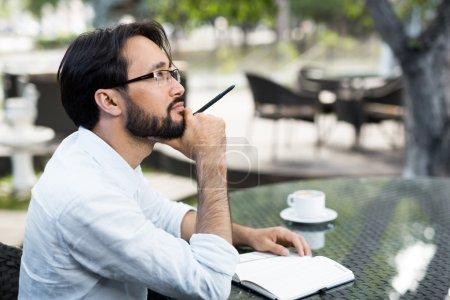 Photo pour Inspiré asiatique homme assis dans un café extérieur - image libre de droit