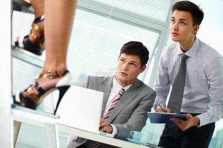 businessmen staring at beautiful female legs