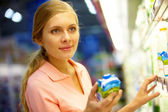 Žena s krabici mléka v obchodu s potravinami