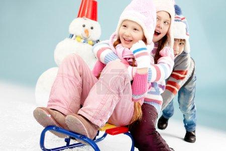 Boy pushing sled with little girls