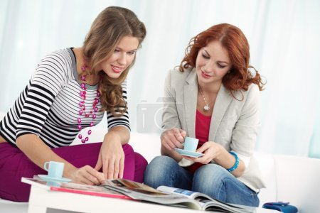 Girlfriends looking through magazines at home