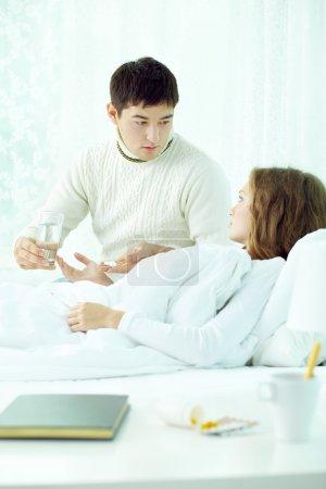 man giving pills to his sick girlfriend