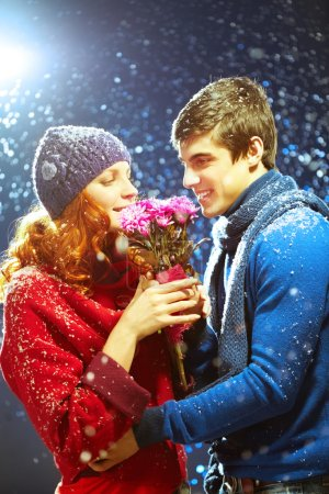 Woman smelling flowers giving by boyfriend