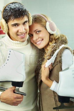 Photo pour Jeune couple avec des patineurs dans la neige en regardant la caméra et souriant - image libre de droit