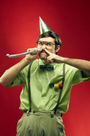 Foto de Retrato de friky en sombrero del partido soplando su nariz en fiesta en horne - Imagen libre de derechos