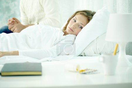 Photo pour Femme malade allongé sur le lit, son mari tenant de sa main - image libre de droit