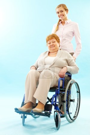 Woman pushing wheelchair with elder woman