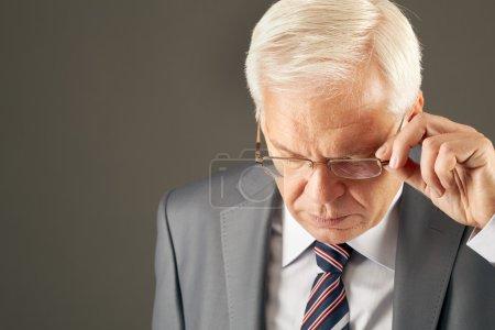 senior man looking through eyeglasses