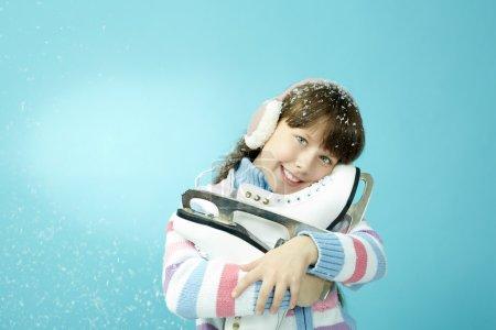 Little girl holding pair of skates