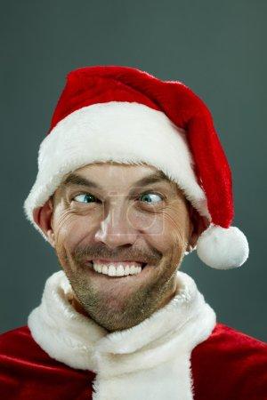 Photo pour Homme en costume du père Noël faire des grimaces et montrant les dents à la caméra - image libre de droit