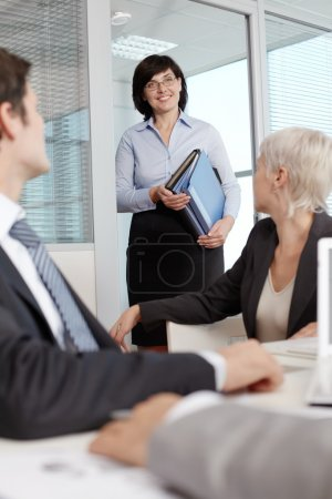 Secretary carrying folders for business people