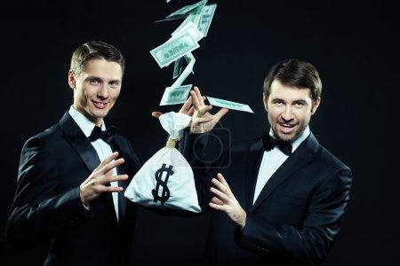 Two magicians making money fly away on black backg...