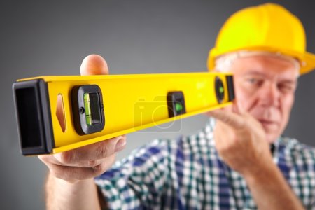 senior constructor holding a ruler