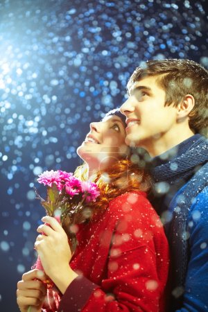 Loving couple looking at snowflakes