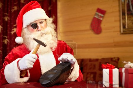 Santa Claus repairing shoe in workshop