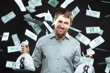 Happy man holding money bags