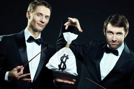 Two magicians doing tricks with sack of money...