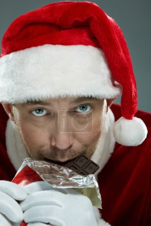 Santa Claus biting bar of chocolate
