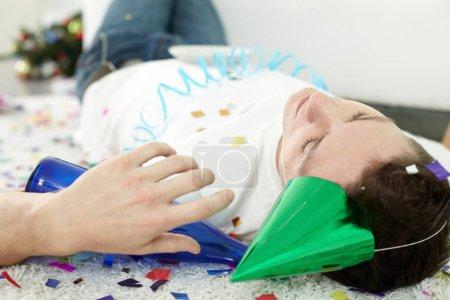 Photo pour Portrait de jeune homme ivre dormant sur le sol en chapeau de fête et avec une bouteille - image libre de droit
