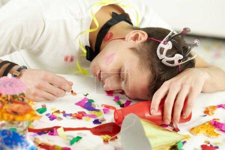 Photo pour Jeune homme en chapeau de fête dormant sur la table parmi les confettis et les restes de nourriture - image libre de droit