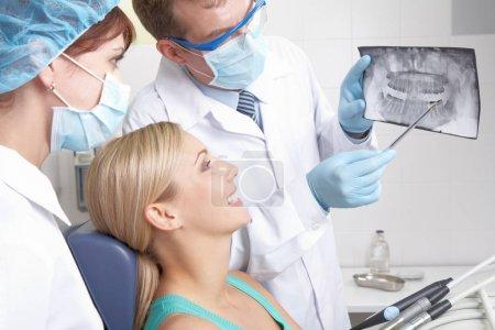 Photo pour Un dentiste montrant un patient sa radiographie des dents - image libre de droit