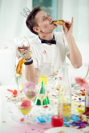 Photo pour Jeune homme ivre, mangeant et buvant des restes de repas de fête après la fête - image libre de droit