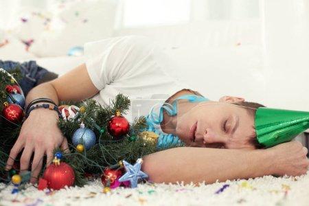 Photo pour Jeune homme ivre, dormir sur le plancher avec arbre de Noël et en chapeau de fête - image libre de droit