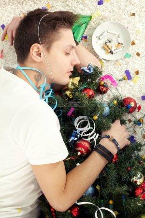 Photo pour Jeune homme ivre dormant sur plancher avec arbre de Noël, après la fête - image libre de droit