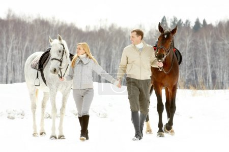 couple leading their horses with reins