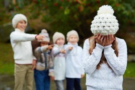 Photo pour Contrarié fille pleurant alors que le groupe d'enfants lui l'intimidation - image libre de droit